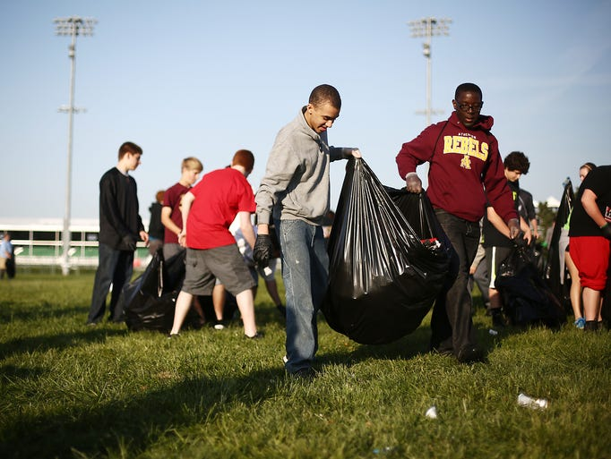 Atherton High School students Jeremy Jackson, right, and Evan Wright clean up in the infield the day after the Kentucky Derby in Churchill Downs. May 4, 2014