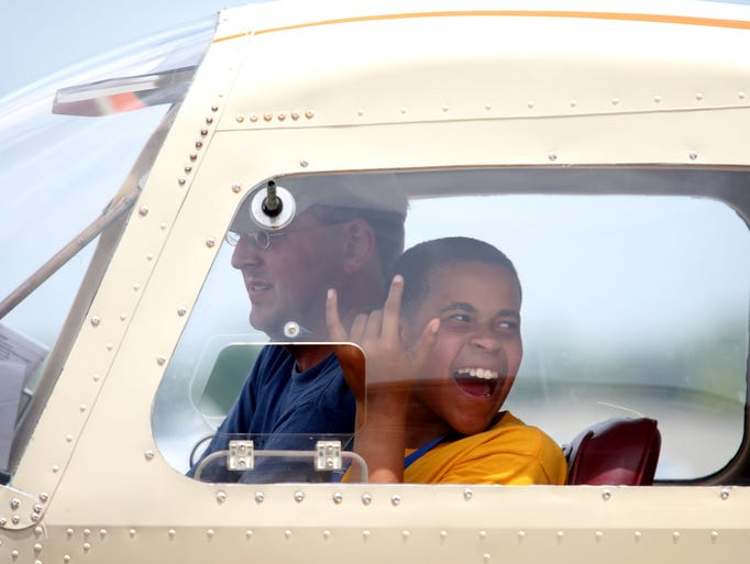 Nathan Colbreath, 12, signals to his friends before riding in a plane at Bowman Field. Colbreath was taking part in the UPS-sponsored Organization of Black Aerospace Professionals Aviation Career Education camp. June 20, 2014.