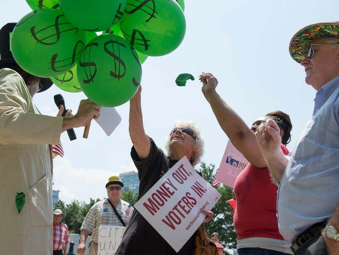 Carol Tvaroh, center, pricks balloons representing money at a rally to limit campaign financing in front of the federal courthouse. The rally featured an Alice in Wonderland themed skit where the Mad Hatter represented Big Money. July 2, 2014