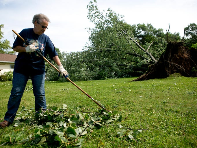 """Holly Webster of Granton rakes leaves and debris in Wendell and Carol Hubing's yard off of Fifth Street in Granton, Monday, Aug. 25, 2014. The silver maple tree was uprooted by storms that hit the Granton area overnight. Webster said, """"I'm so impressed. This has never happened to Granton before and you hear about communities coming together and here we are."""""""