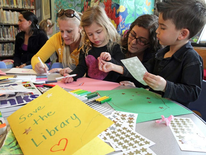 Alexis Lean, center, and Cooper Steinberg, at right, both 4,  work on cards with their nanny's Monika Nicola, second from left, and Vanessa Morales, second from right, during a crafting activity at the Purchase Free Library April 25, 2014. For the last 60 years the library has been housed in the quaint stone building of the Purchase Community Center, a day camp and after-school recreation program, that says because of safety concerns it is seriously considering ending the library's tenancy.