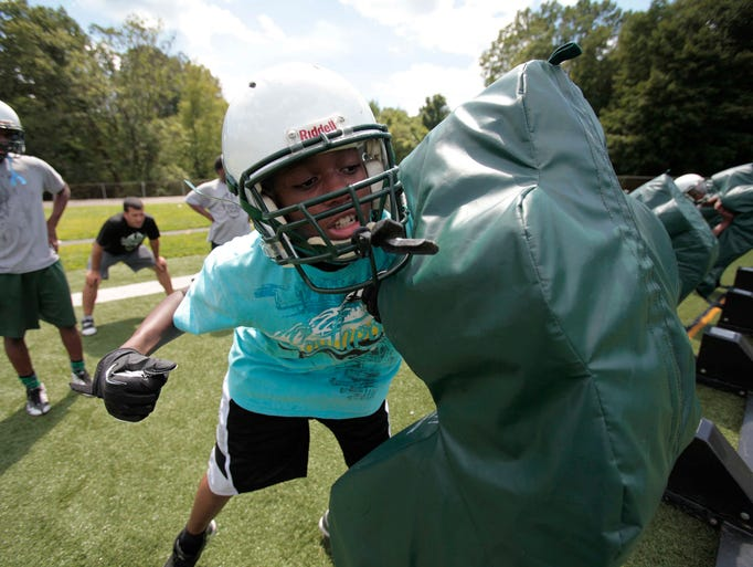 Daveitto McKenzie hits a blocking sled during the first day of practice at Woodlands High School in Greenburgh Aug. 18, 2014.