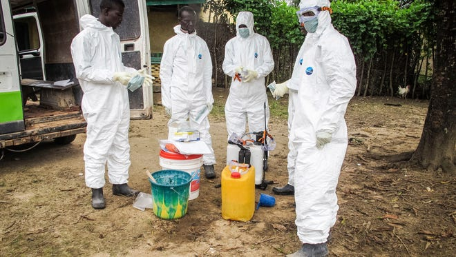 Health workers wear protective gear before entering the house of a person suspected to have died of the Ebola virus in Port Loko Community on the outskirts of Freetown, Sierra Leone, on Oct. 21, 2014.