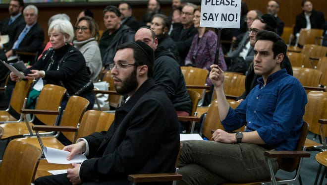 Moshe Deutsch of Lakewood holds a sign to let the board know his thoughts. Residents of Lakewood attend a planning board meeting where a discussion involving the rehabilitation of commercial properties along a portion of County Line Road took place. Many residents of the area complained of traffic congestion. 