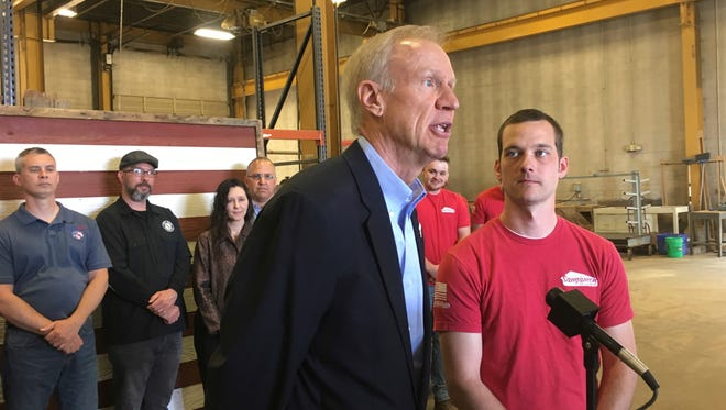 Gov. Bruce Rauner, center, speaks to reporters on May 1, 2018, in Springfield, Ill.