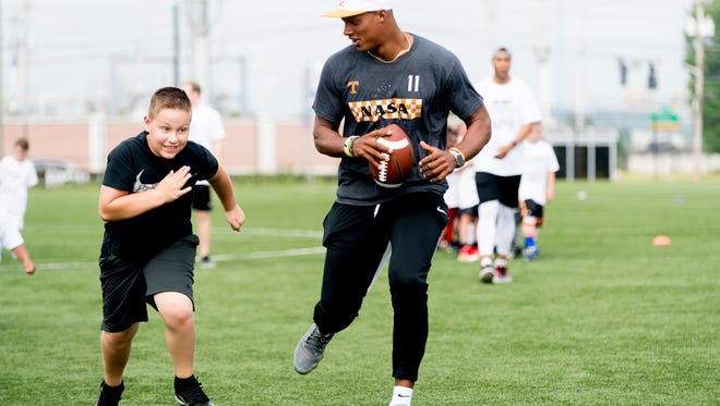 Josh Dobbs does a drill with Ryder Ogle, 10, of Pigeon Forge, at Dobbs' football camp at Sansom Sports Complex in Knoxville, Tennessee on Saturday, June 2, 2018.