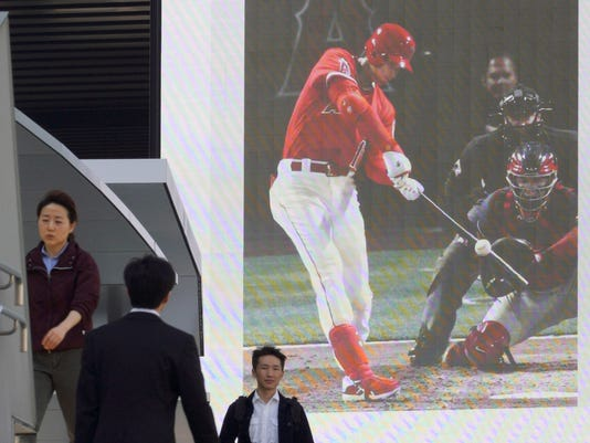 Pedestrians walk past a huge monitor showing a news photo of Los Angeles Angels' Shohei Ohtani hit a three-run home run against the Cleveland Indians, in Tokyo Wednesday, April 4, 2018. Ohtani hit his first major league home run in his first Angel Stadium at-bat. (AP Photo/Eugene Hoshiko)