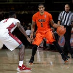 Oregon State guard Malcolm Duvivier (11) dribbles next to Stanford guard Christian Sanders (1) during the first half of an NCAA college basketball game Thursday, Feb. 11, 2016, in Stanford, Calif.