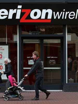 People pass by a Verizon Wireless store in San Francisco.