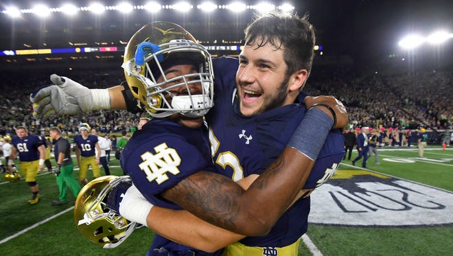 Notre Dame safety Isaiah Robertson (17) and offensive lineman Robert Hainsey (72) celebrate a win over USC.