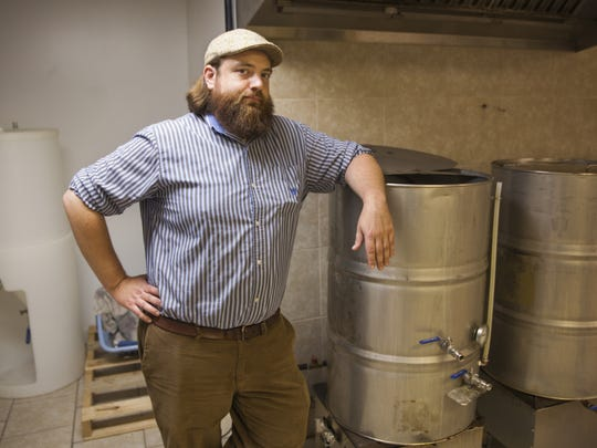 Jonathan Wright, owner of Redbeard Brewing Company, stands next to his beer brewing vats on Oct. 12, 2014.