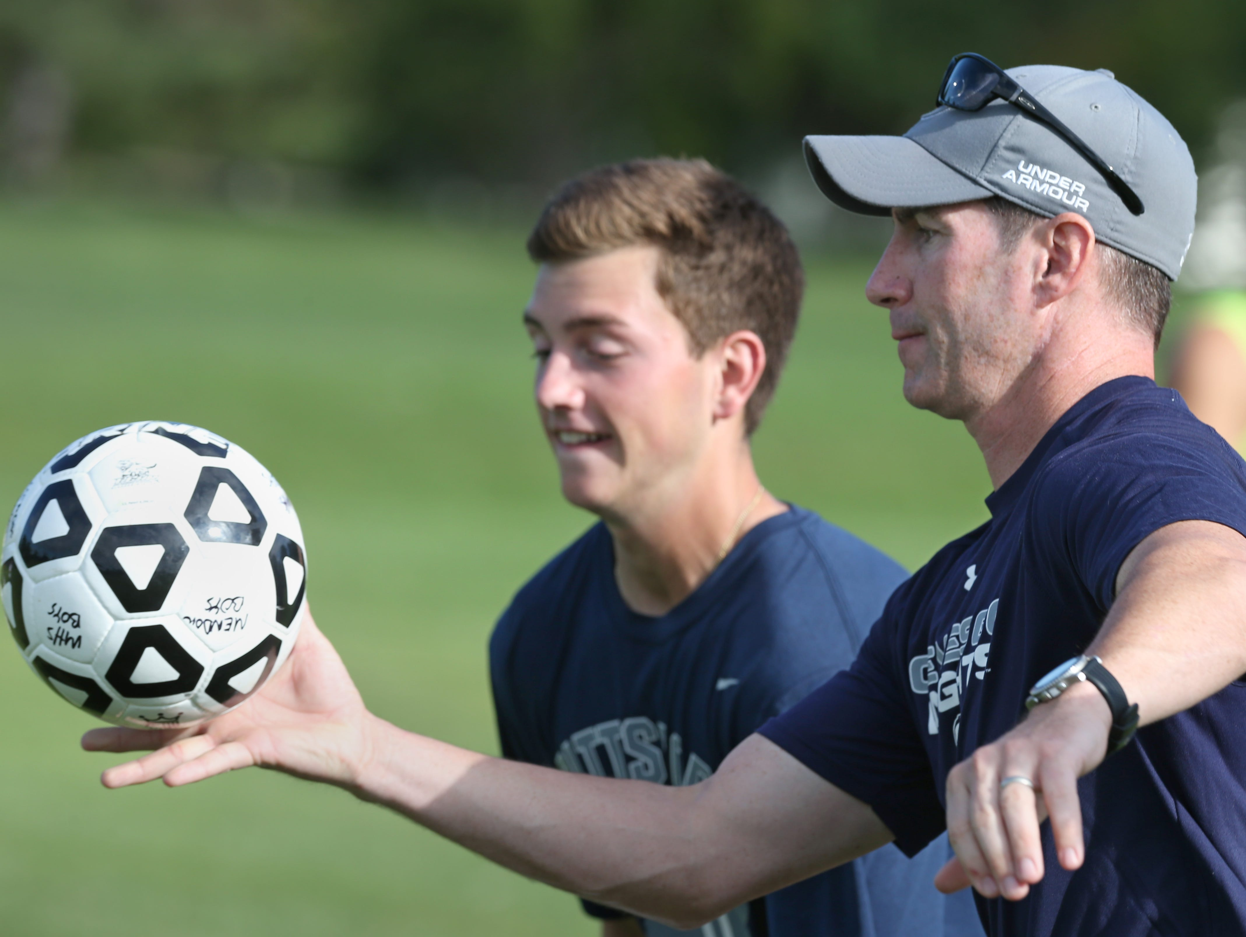 Pittsford Mendon boys varsity soccer coach Mark Hurley boots the ball downfield as he leads the team through practice at Hopkins Park in Mendon Tuesday, Sept. 22, 2015.