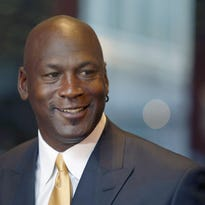 In this Aug. 21, 2015, file photo, former NBA star Michael Jordan smiles at reporters in Chicago. Spokespeople for Jordan and the Jewel-Osco supermarket chain say there's a settlement regarding the alleged misuse of the basketball star's name. The case involves the use of Jordan's name in a 2009 Sports Illustrated ad. In August, a jury awarded Jordan $8.9 million from the now-defunct Dominick's for using his name in a similar ad.