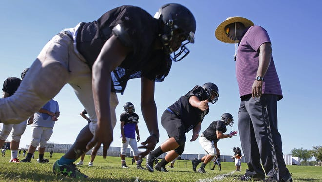 Copper Canyon football head coach Shawn Kemmer  works with his team during practice on Tuesday, Aug. 23, 2016 in Glendale.