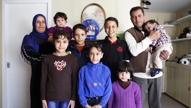 The Alhamoud family poses for a portrait in their Hamilton County home Friday, November 13, 2015. They arrived in Cincinnati on October 19, 2015, from Jordan, where they sought refuge for several years after fleeing Syria. The Enquirer/Meg Vogel