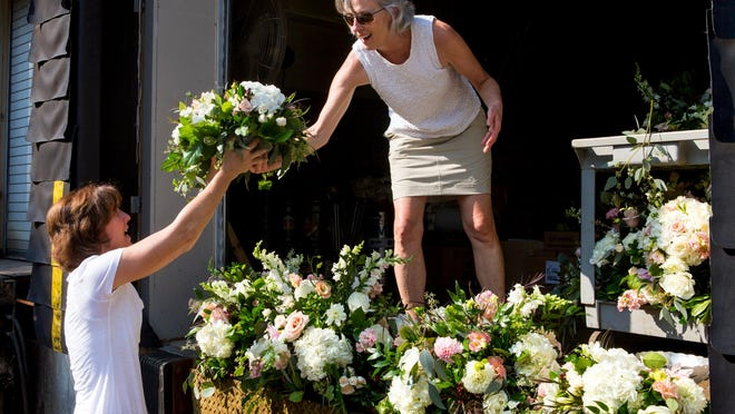 Cathleen Fagan hands Terri Wellman a wedding centerpiece on the loading dock of the Cincinnati Art Museum. Fagan and Wellman are volunteers with ReBloom, an organization in partnership with Robin Wood Flowers that re-purposes donated flowers after weddings and delivers them to hospital patients and other nonprofit organizations in Greater Cincinnati.