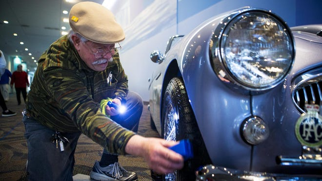 Tim Ross cleans the tires of his 1963 Austin Healey 3000 at the Cincinnati Auto Expo inside the Duke Energy Convention Center in 2016.