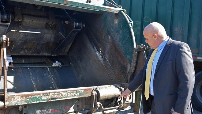 Jacob Tawil, Middletown's commissioner of Public Works, demonstrates a tipper that is used to help sanitation workers dump trash into the back of a garbage truck. Two of the city's four trucks have a tipper device on the back.