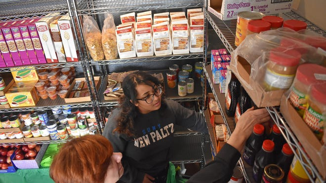 Serena Cruz, right, a sophomore and volunteer at the Student Christian Center Food Pantry at SUNY New Paltz, helps the food pantry's director, Rev. Dianna Smith, organize and refrigerate items on Friday in the Student Union.