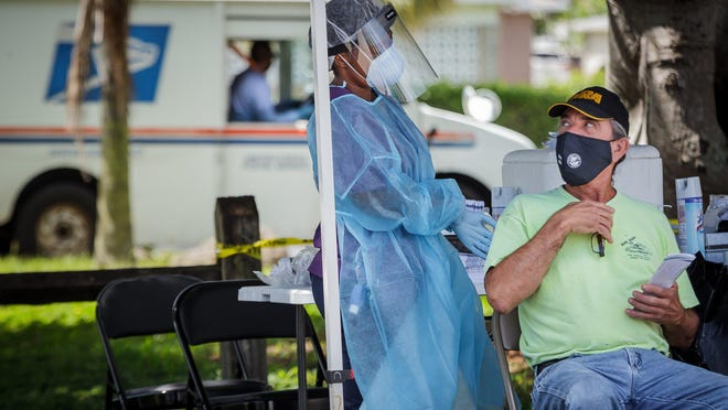 Nurse practitioner Guerlyne Estime readies to perform a nasal swab Friday during a COVID-19 testing event under a tent at a C.L. Brumback Primary Care Clinic of the county Health Care District at Sunset Ridge Park in Lake Worth Beach.
