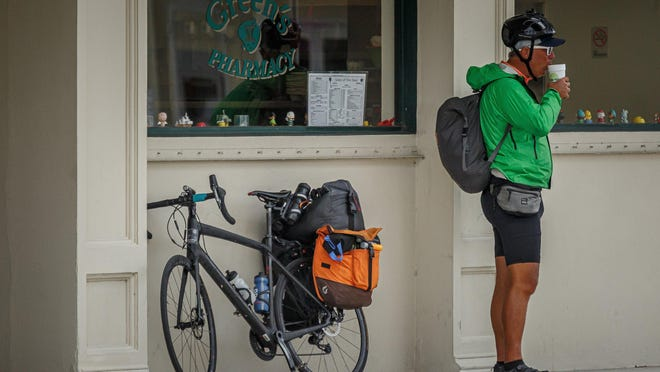 A cyclist sips a beverage from Green's Pharmacy in Palm Beach on Saturday. Island pharmacies have continued to operate during the coronavirus pandemic.