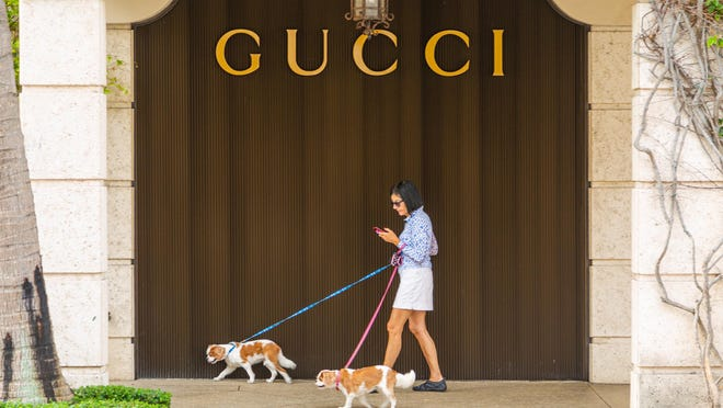 A woman walks her two dogs past a closed Gucci store, one of the businesses shuttered on Worth Avenue because of the coronavirus pandemic.