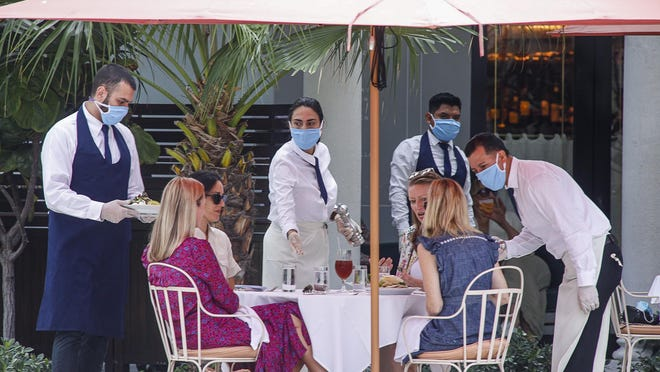 A group of women are served their lunch by mask-wearing employees Monday at Sant Ambroeus.