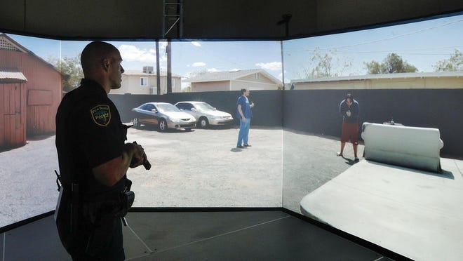 """Palm Beach police officer Chris Murphy hones his skills inside the department's new VirTra 300 simulator on Thursday. Referring to the 300-degree law enforcement small arms simulator, Palm Beach police spokesperson Michael Ogrodnick said, """"It teaches our officers to deescalate situations and to think clearly when under stress."""""""