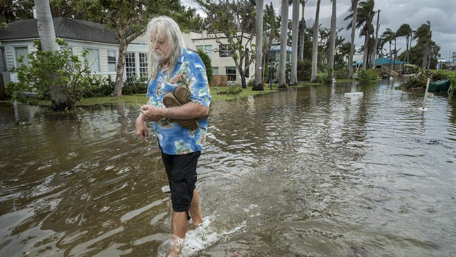 C.J. Johnson wades from his home on Marine Way after king tides flooded the street and brought water into his home in Delray Beach in October 2017. Scientists say such flooding will become more common as climate change raises the sea level.
