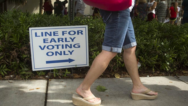 Amy Gibson of Palm Beach Gardens waits in line to vote at the Gardens Branch Library on Sunday, the last day of early voting.