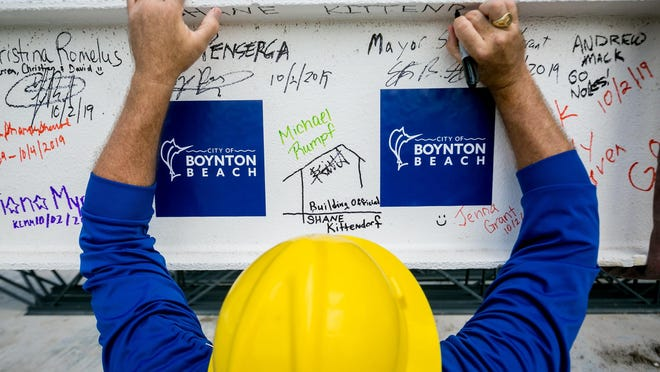 Boynton Beach building official Shane Kittendorf signs a 1,400 pound, 40 foot long steel beam that will be housed in the City Commission Chambers? ceiling, during a topping out ceremony for the new City Hall & Library in Boynton Beach on October 2, 2019.