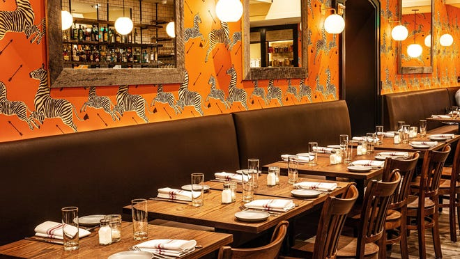 Almond's dining room features mocha seating and Scalamandre jumping-zebra wallpaper in a vibrant orange hue.