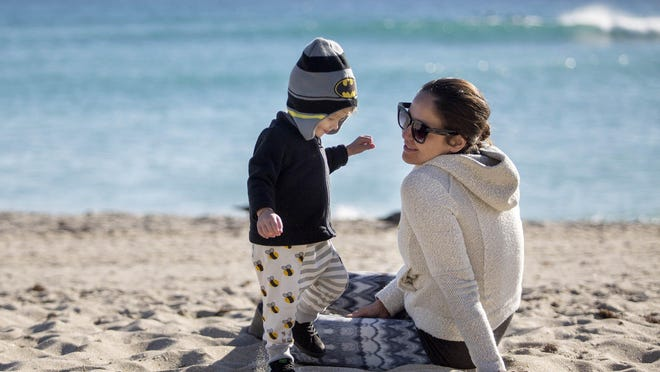 Maura Koons and her son Ocean Rain Koons wear sweaters to keep warm on Lake Worth Beach in 2018.