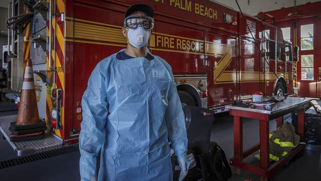 West Palm Beach Fire Rescue personnel show some of the gear and procedural precautions they're taking during emergency response calls in a demonstration Friday at West Palm Beach Fire Rescue Station 5 . Firefighter, Niko Green, models the protective gear that rescue personnel wear for protection against possible coronavirus exposure. Amid the COVID-19 pandemic 911 calls have increased in the area, said Fire Chief Diana Matty.