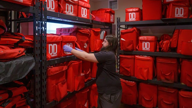 Delivery Dudes personnel create instructional video content for coronavirus procedures at the Delray Beach, Fla., headquarters on Friday, March 20, 2020. Lounge manager Mike Castillo, Delray Beach, stows thermal food delivery bags at the office.