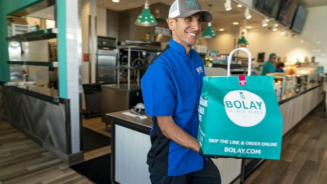 Operating partner J.T. Testa hands a food order to a customer at Bolay in West Palm Beach, Florida on March 20, 2020. Gov. Ron DeSantis declared that restaurants can only do pick-up and delivery. [GREG LOVETT/palmbeachpost.com]\r\r\r\r