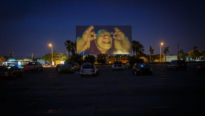 Moviegoers attend the Lake Worth Drive-In in Palm Springs, Fla, on Tuesday, despite an order that indoor movie theaters across the county had to close