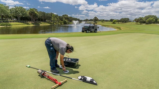 Zevin Lopez puts in the cup on the 18th hole at the Abacoa Golf Club in Jupiter, Florida on April 28, 2020. Parks, golf courses, marinas, boat ramps, community pools, and other recreational activities will reopen in Palm Beach County on Wednesday.