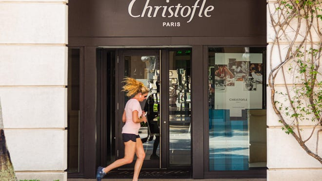 A jogger passes the Christofle store Tuesday on a deserted Worth Avenue. All of the stores on Worth Avenue are temporarily closed due to the coronavirus pandemic.
