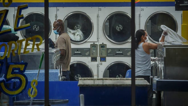 Customers tend to their laundry Tuesday during the coronavirus crisis at Express Laundry on Broadway at 25th Street in West Palm Beach.