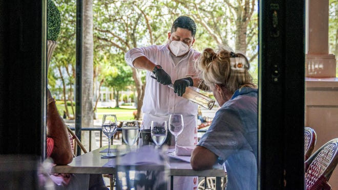 Server Oscar Vicente opens a bottle of wine for customers dining at Pistache in West Palm Beach, Florida on Monday, May 11, the first day restaurants in the county were able to serve in the dining room and outside seating.