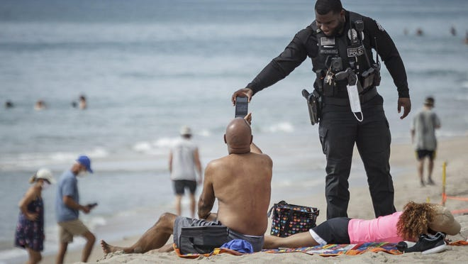 A Delray Beach Police Department officer reminds beachgoers that sunbathing is not allowed at the municipal beaches on Monday.