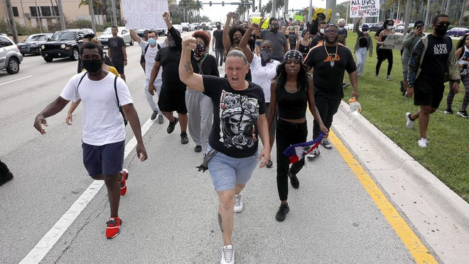 A group takes part in a George Floyd protest that began at West Palm Beach city hall and then weaved its way around the downtown area for several hours on Tuesday.
