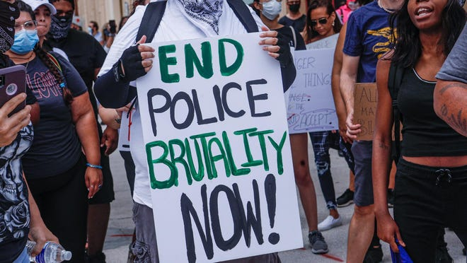 A George Floyd protestor holds up a sign during a march that began at West Palm Beach city hall and weaved its way around the downtown area for several hours Tuesday afternoon, June 2, 2020.
