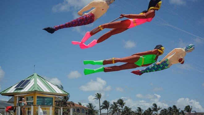 """Larger-than-life kites fly above Delray Beach Ocean Rescue lifeguard Alicia Warren Friday in Delray Beach. The kites were flown by Winfred Randolph Lowe, aka """"Randy the Kite Man."""""""