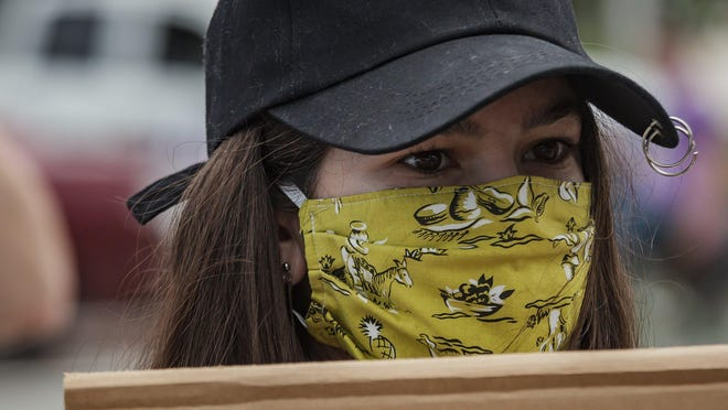 A protester in Jupiter wears a mask to protect against coronavirus spread during a march along Indiantown Road Tuesday. More than 150 people marched for social justice and racial equality.