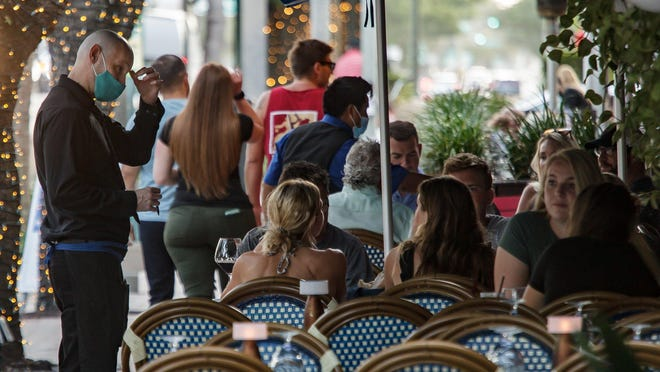 A masked server waits on patrons at Tramonti on Atlantic Avenue in Delray Beach on Thursday, June 25. The tables were spread apart to meet social distancing guidelines.