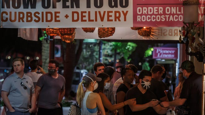 Patrons pick up their orders at Rocco's Tacos on Clematis Street in downtown West Palm Beach, Fla., on Tuesday, May 5, 2020.