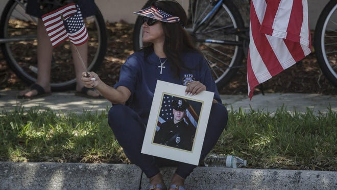 Jacqueline Kerik hold a photo of her son who works for the Newark Police Department during a pro Trump rally Monday in Boca Raton. Over one hundred people gathered near Boca Raton City Hall to show support for President Donald Trump and the police departments.