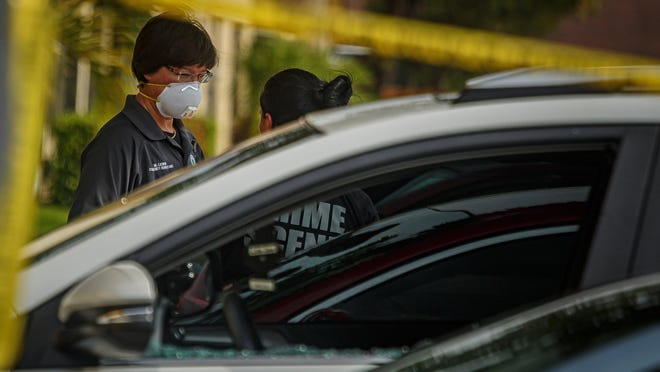 Palm Springs police personnel investigate the fatal shooting of Shatorria Manuel-Francois, 26, in front of a white Toyota RAV4 that is sealed in red crime-scene investigation tape on the 400 block of Springdale Circle on Friday, April 24, 2020, in Palm Springs.